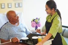 Älterer männlicher Patient, der Mahlzeit im Krankenhaus-Bett gedient wird Lizenzfreie Stockfotos