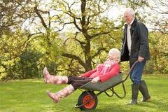 Älterer Paar-Mann, der Frauen-Fahrt in der Schubkarre gibt Stockbilder
