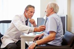 Älterer Patient, der medizinische Prüfung mit Doktor In Office hat Lizenzfreies Stockbild
