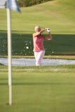 Älterer weiblicher Golfspieler, der Bunker-Schuß spielt Stockbilder