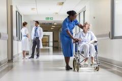 Älterer weiblicher Patient im Rollstuhl u. in der Krankenschwester im Krankenhaus Stockbilder