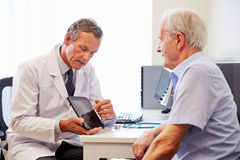 Älteres geduldiges, Beratung mit Doktor In Office habend Lizenzfreie Stockfotografie