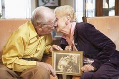 Älteres Paarholding-Hochzeitsfoto Stockbild