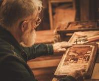 Älteres Stärkungsmittel, das mit antikem Dekorelement in seiner Werkstatt arbeitet Stockfoto
