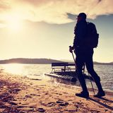 LTourist on beach at old paddle boat. Man with poles  in warm sporty clothing at sunset. Autumn weather. Royalty Free Stock Image