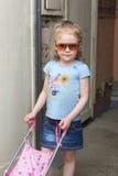 Lttle flicka i solglasögon med en leksaksittvagn royaltyfria bilder