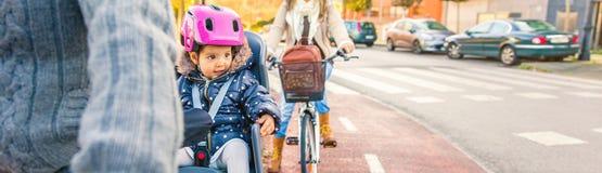 Lttle flicka med hjälmen på head sammanträde i cykelplats arkivfoto