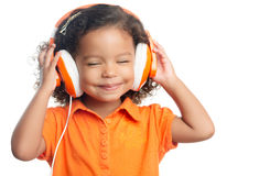 Lttle girl with an afro hairstyle enjoying her music on bright orange headphones Stock Photos