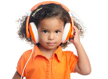Lttle girl with an afro hairstyle enjoying her music on bright orange headphones Stock Photo
