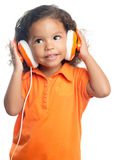 Lttle girl with an afro hairstyle enjoying her music on bright orange headphones Royalty Free Stock Photography