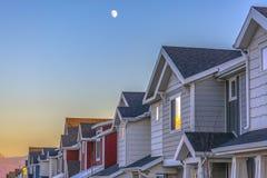 Lua acima das casas de parede-meia no por do sol no vale de Utá imagem de stock