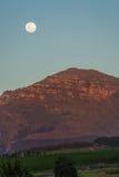Lua acima de uma montanha no por do sol Imagens de Stock