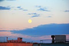 Lua acima dos telhados da cidade Fotografia de Stock Royalty Free