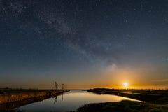 A lua brilha no porto em Skärlöv, com a Via Látea que desvanece-se afastado Imagens de Stock