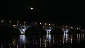 A Lua cheia aumenta sobre a ponte Ponte da estrada entre as cidades de Saratov e Engels, Rússia O Rio Volga filme