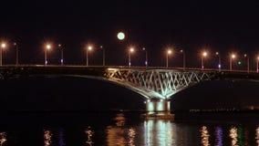 A Lua cheia aumenta sobre a ponte tempo-lapso Ponte da estrada entre as cidades de Saratov e Engels, Rússia O Rio Volga video estoque