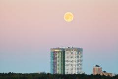 Lua cheia no céu cor-de-rosa sobre casas urbanas Foto de Stock