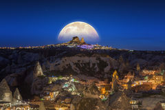 Lua cheia que aumenta acima do castelo de Uchisar em Cappadocia, Turquia Fotografia de Stock