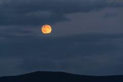 Lua cheia que aumenta atrás das nuvens fotografia de stock royalty free