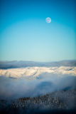 Lua cheia sobre montanhas nevado Fotografia de Stock