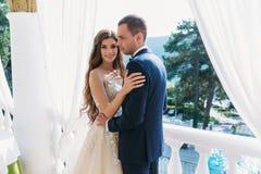 Lua de mel bonita dos pares que abraça-se e que está em um balcão branco Os jovens preparam em um terno e em um a pretos Foto de Stock