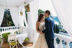 Lua de mel bonita dos pares que abraça-se e que está em um balcão branco Os jovens preparam em um terno e em um a pretos Foto de Stock Royalty Free