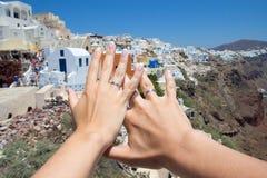 Lua de mel na ilha de Santorini - mãos com alianças de casamento sobre o pa Fotografia de Stock Royalty Free