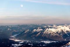 A lua sobre montanhas nevado Foto de Stock Royalty Free