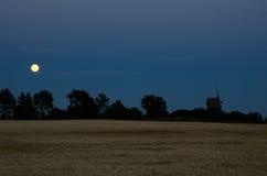 Lua sobre o moinho de vento e um campo de milho Imagem de Stock Royalty Free