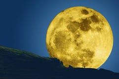 A lua super mostra em silhueta a montanha e um homem Fotografia de Stock Royalty Free