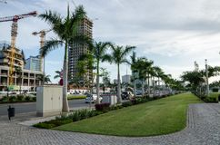 Luanda, Angola - April 28 2014: Luanda`s promenade with palms and construction of modern high rise buildings at sea side. Of capital stock image