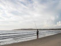 Luanda, Angola - April 26, 2014: Recreatieve jonge visser die zich bij het strandnoorden bevinden van de hengelsport van Luanda,  royalty-vrije stock afbeeldingen