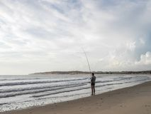 Luanda, Angola - April 26, 2014: Recreational young fisherman standing at beach north of Luanda angling, Angola, Africa.  royalty free stock images