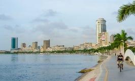 Luanda, Angola - 28 de abril de 2014: Baía de Luanda com passeio e homem do beira-mar na bicicleta imagens de stock