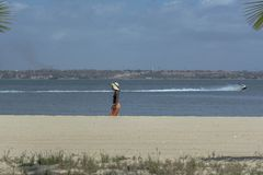 Luanda/Angola - 11 11 2018: View at the beach on Mussulo Island, with a woman walking, water with a boat jet, Luanda city and the. Sky as background royalty free stock images