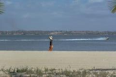 Luanda/Angola - 11 11 2018: Visión en la playa en la isla de Mussulo, con una mujer caminando, agua con un jet del barco, ciudad  imágenes de archivo libres de regalías