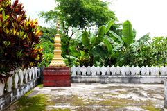 golden buddhist stupa with lush tropical vegetation and an old balcony with nice pattern around it stock photos