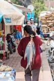 LUANG PRABANG, ΛΆΟΣ - 11 ΙΑΝΟΥΑΡΊΟΥ 2017: Μια γυναίκα φέρνει τα μεγάλα ψάρια πίσω από την πίσω κάθετος Στοκ εικόνες με δικαίωμα ελεύθερης χρήσης