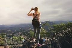 LUANG PRABANG, ЛАОС - 29-ОЕ ИЮНЯ 2018 - азиатский женский турист фотографирует заход солнца поверх горы Phousi в Luang Prabang, Л стоковое фото rf