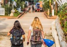 LUANG PRABANG, ЛАОС - 11-ОЕ ЯНВАРЯ 2017: 2 девушки на улице города задний взгляд Скопируйте космос для текста стоковое фото