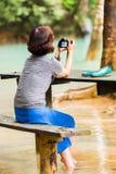 LUANG PRABANG, ЛАОС - 11-ОЕ ЯНВАРЯ 2017: Женщина около Kuang XI падает, водопад в горе зоны с космосом экземпляра леса для текста Стоковые Изображения RF