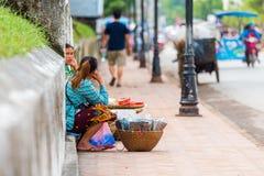 LUANG PRABANG, ЛАОС - 11-ОЕ ЯНВАРЯ 2017: Женщина продавая еду на улице города Скопируйте космос для текста Стоковые Фото