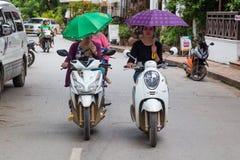 Luang Prabang, Лаос - около август 2015: Девушки управляя мотоцилк на улицах Luang Prabang, Лаоса Стоковая Фотография