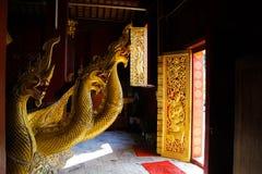 LUANG PRABANG WAT XIENG THONG, LAOS - DECEMBER 17. 2017: Dragon statues inside temple illuminated by natural sunlight stock photo