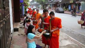 LUANG PRABANG, LAOS - APRIL 2014: Leute geben den Mönchen Reis stock video