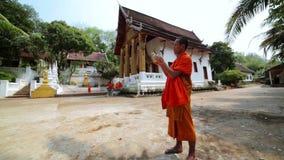 LUANG PRABANG,LAOS - APRIL 2014: monk libaretes bird. Day time stock video footage