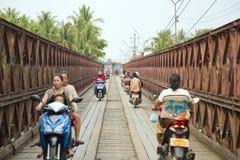 LUANG PRABANG, LAOS - APRIL 2014: mopeder som korsar den historiska järnbron Royaltyfria Foton