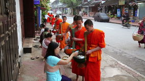 LUANG PRABANG, LAOS - APRIL 2014: people give rice to monks