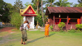 LUANG PRABANG,LAOS - APRIL 2014: tourist taking picture of monk stock video footage