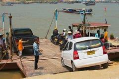 People embark car to a local ferry boat at Mekong river bank in Luang Prabang, Laos. LUANG PRABANG, LAOS - APRIL 12, 2012: Unidentified people embark car to a royalty free stock photo
